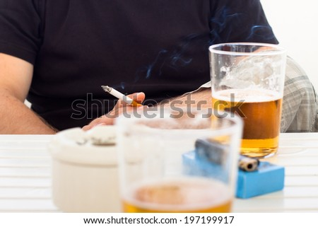 Detail of young man with cigarette and glass of beer.
