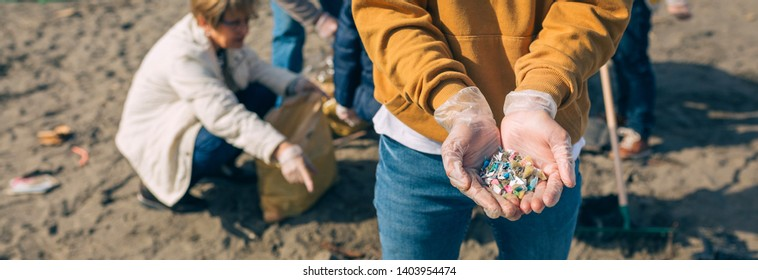 Detail of young man hands showing microplastics on the beach
