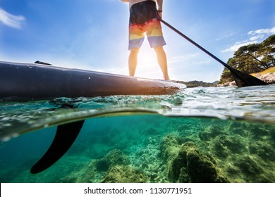 Detail of young man on paddleboard, half under and half above water composition. Paddleboarding is the modern way of transportation and water activity sport.