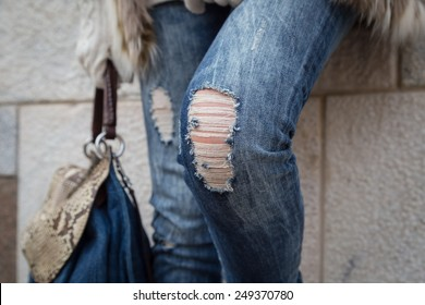 Detail of a young woman with bag posing in the city streets