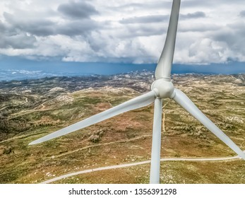 Detailed aerial view, by drone, of a wind turbines on top of mountains, dramatic sky as background, in Portugal