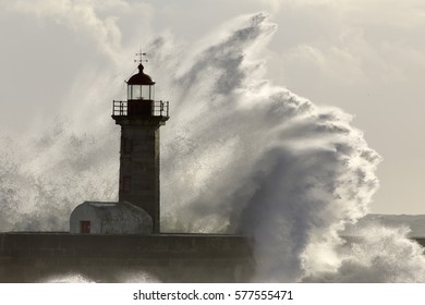 Detailed big stormy sea wave splash over lighthouse. Douro river mouth, Porto, Portugal.