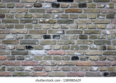 Detailed Brick wall texture background with color variations of black, earthy, reddish and white.