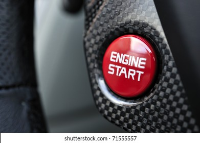 Detailed close up of a engine starting button surrounded by carbon fibre