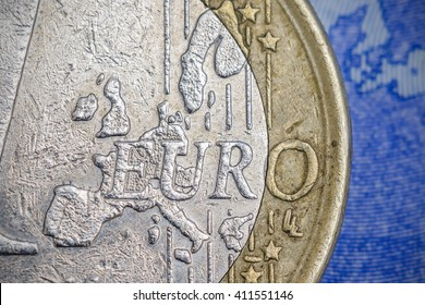 "Detailed close up of ""Euro"" lettering on an one euro coin and a twenty euro banknote in background"