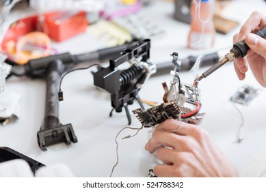 Detailed close up of mans hands working with drone chips