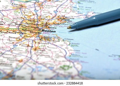 Detailed closeup map of Boston and pen pointing to destination for travel