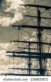 Detailed closeup of mast rigging top on sail boat during cruise, shot on dark sepia sky. Marine objects concept.