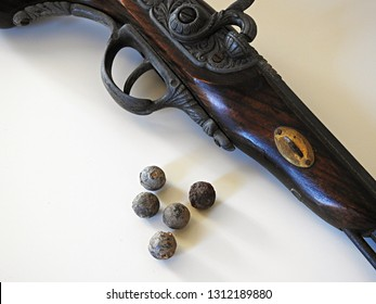 Detailed closeup of musket balls (bullets) and antique wooden flintlock pistol displayed on white surface and background. Decorative vintage/historic weapon concept with copy space