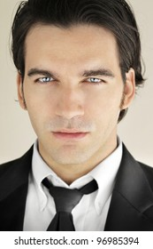 Detailed close-up portrait of a great looking male model in formal black suit and tie with bright blue eyes