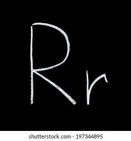 Detailed macro shot of chalkboard letter R isolated on black