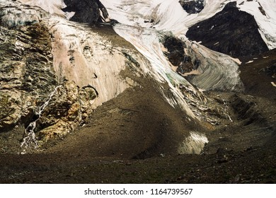 Detailed natural texture of giant rock of fantastic shape covered with snow and ice in highlands. Small waterfalls and brooks flow down mountainside. Fantasy mountain landscape of majestic nature.