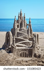 A detailed, ornate sand castle with water behind.
