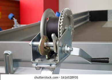detailed photo of the construction of a small metal mechanical wire rope winch with a stainless steel hook