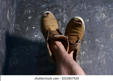 Detailed photo of shoes with holes in them and toes sticking out