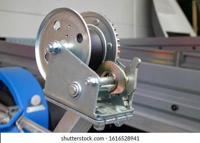 detailed photo of a small metal mechanical rope winch with a stainless steel hook