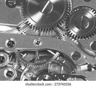 A detailed shot of a clockwork. Image in black and white.