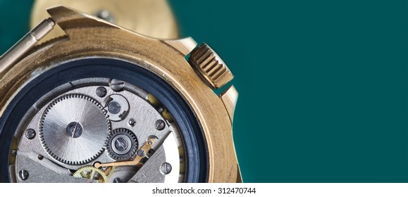 Detailed view of ancient clock parts. Macro shot of the interior of an old pocket watch with a hand-wound mechanical movement. copy space. dark green background.
