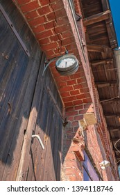 Detailed view of the brick facade of an old farmhouse with a clock and a wooden gate used for loading and unloading the barn and storage.