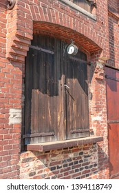 Detailed view of the brick facade of an old farmhouse with a clock and wooden gates used for loading and unloading the barn and storage.