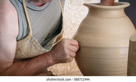 Detailed view of craftsman hands working on pottery wheel