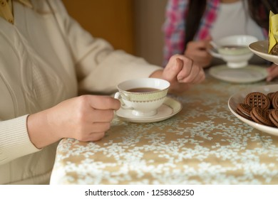 Detailed View Of Delicate Cup Of Coffee Standing On A Plate. Woman's Hands And Cup Of Coffee On The Table.