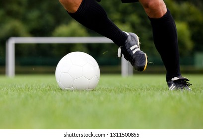 Detailed view of a footballer / soccer player dribbling the ball. Selective focus.