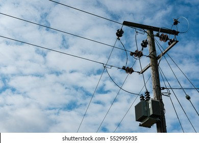 Detailed view of a high power electrical cabling system seen atop a utility pole.
