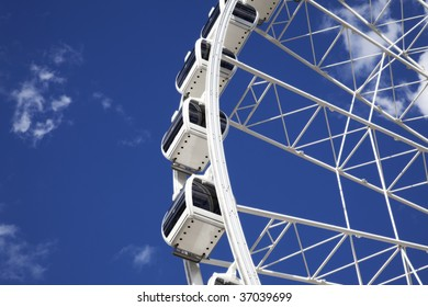 A detailed view of a large white ferris wheel against a beautiful blue sky