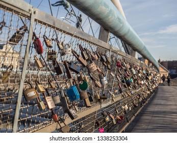 The detailed view of lovelocks hanged on the footbridge Bernatek in the center of Krakow. Krakow, Poland.