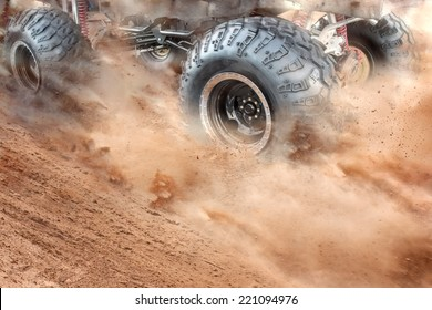 Detailed view of motion the wheels tires and off-road truck shaft that goes in the dust of the desert  through the wheels on the sand