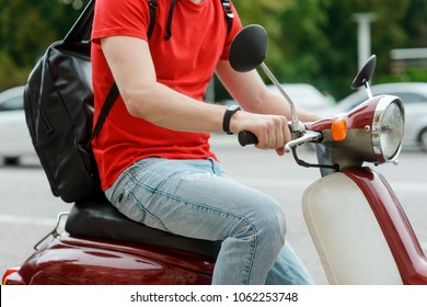 Detailed view on a young man driving an old-fashioned motorbike, running through city streets.