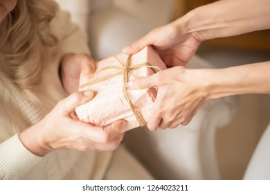 Detailed View Of A Present In Pink Wrapper In The Hands Of Women. Close Up Shot Of A Precious Gift.
