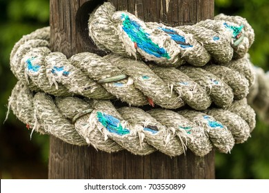 detailed view of a thick old rope frayed and worn on a wooden bollard in the harbor of Plymouth in Massachusetts