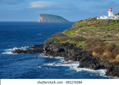 Detailed view of volcanic coast, lighthouse and goat island in Terceira, Portugal
