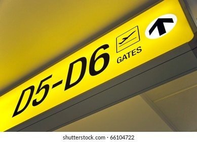 Detailed view of yellow airport departure sign showing direction to gates.