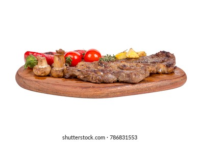Detailed view of yummy tasty grilled steak served on wooden plate with potato, tomato and red pepper, isolated on white background.