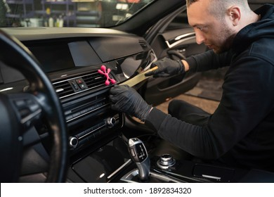 Detailing worker pasting protective tape on the car interior trim before polishing