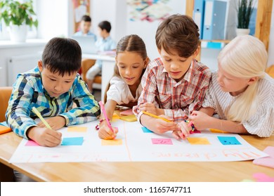 Details. Attentive funny children drawing a poster while being at school