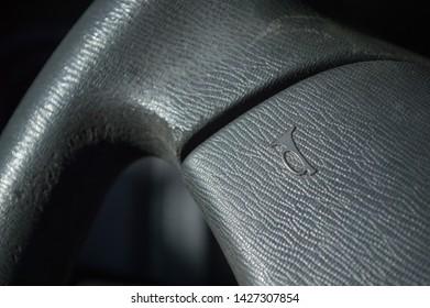 details of black car steering wheel, showing the horn, honk, hooter symbol