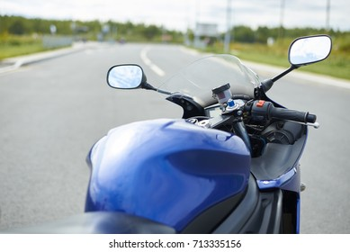 Details of body of modern powerful motorcycle on empty road with copy space for your text or advertising conctent. Outdoor summer shot of custom-built blue motorbike. Transport and extreme lifestyle.