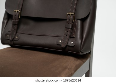 Details of brown men's shoulder leather bag for a documents and laptop on a brown chair with a white background. Mens leather brief case, messenger bags, leather satchel, handmade briefcase.