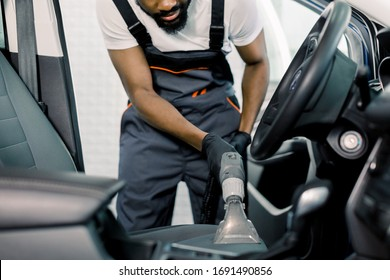 Details of car vacuum cleaning. African professional male worker using wet vacuum cleaner for dirty car interior. Auto car service cleaning the drivers seat, cleaning and vacuuming leather