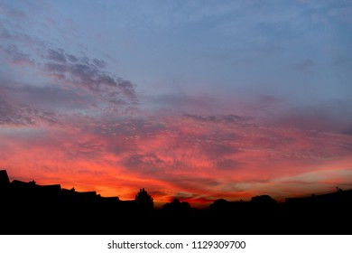 Details of clouds at sunset with dark orange, pink, and blueish purple tones above the silhouette of houses in the darkness