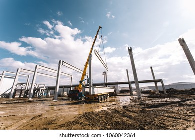 Details of construction site with crane lifting prefabricated concrete framework, unloading and cargo details