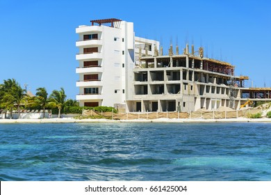Details of a construction site of a residential building in front of turquoise caribbean sea, clear blue sky in background and green palms moving in the wind, as concept o a dream home in paradise.