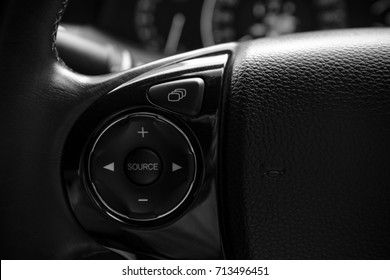 details of controller bottons on steering wheel of modern car, display control botton, audio control bottons and horn icon, black and white photography