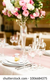 Details of decoration of Groom's and Bride's wedding table on wedding party. Decoration by pink fabric and flowers. Bonbonnieres with honey for guests