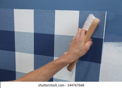 details of decorator hanging wallpaper with work tool in motion