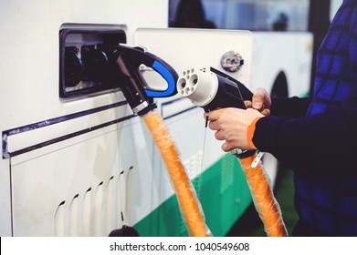 Details of electric vehicle charging city bus transport. Green and renewable energy sources. man holds in his hand.